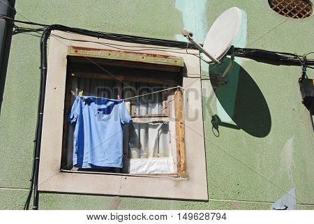 House window with clothes and satellite antenna.