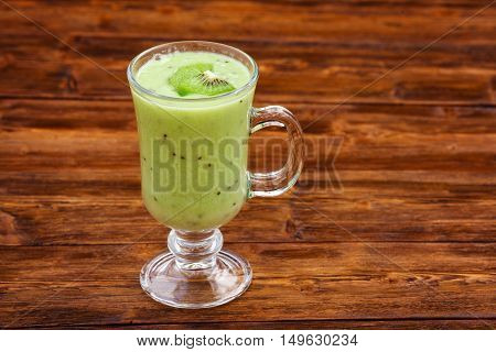 Apple and kiwi fruit milk smoothie in a glass, wooden background. Healthy food concept