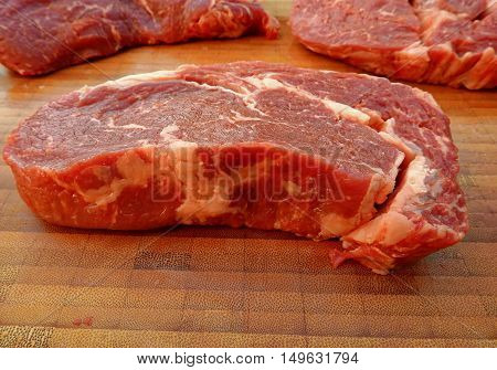 Photos in which some raw beef steaks in the kitchen