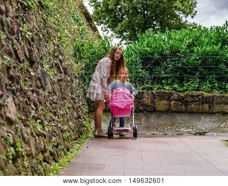 Two sisters with babycarrier for dolls outdoor. Childhood concept