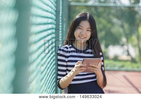 asian girl and computer tablet in hand standing with toothy smiling face