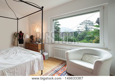 Interior, lovely bedroom with double bed in wrought iron