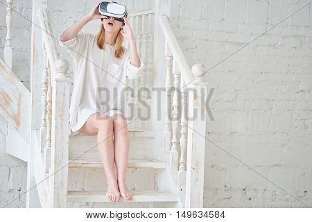The girl in white sitting on the stairs at home in a virtual reality helmet