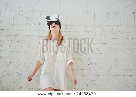 The girl in white standing against a white wall in a virtual reality helmet