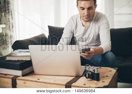 Man sitting on a sofa working on laptop