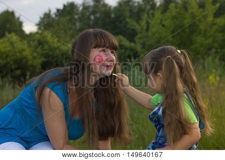 little daughter draws crayons on face mom outdoors