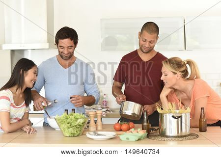 Friends having fun cooking meal together
