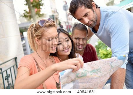 Group of friends on vacation reading city map