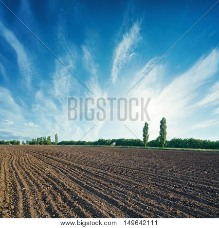 black agricultural field and sun in cloudy sky