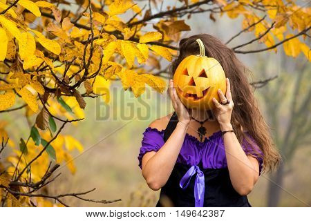 Fancy woman on Halloween in the forest holding in hands pumpkin with carved face having fun on traditional autumn holiday decorating home.
