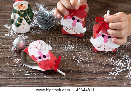 The Child Create A Greeting Packaging For Candy Santa Claus On Paper. Children's Art Project, A Craf