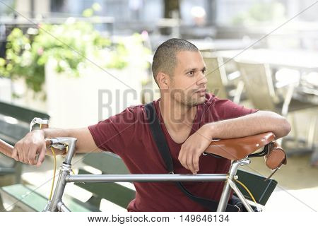 Man with bicycle sitting on park bench