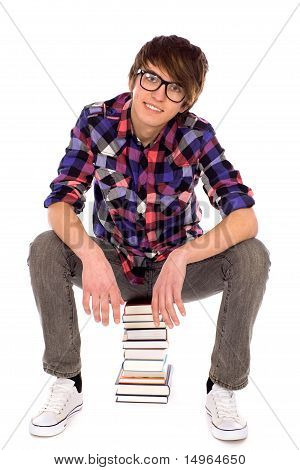 Young man sitting on pile of books