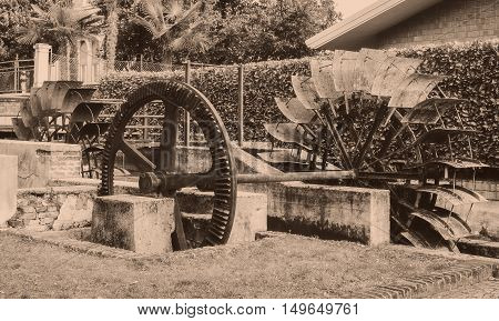 Old Wheels Of A Watermill. Vintage Style Picture. Adding Grain To Give An Old Photo Effect.