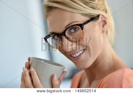 Portrait of middle-aged woman with eyeglasses drinking tea