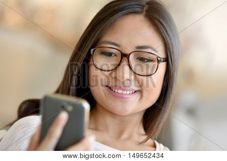 Asian girl relaxing at home connected wih smartphone