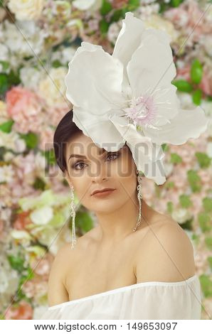 girl with a large and unusual flower on the head sits with a white blouse of a decollete looks in a camera
