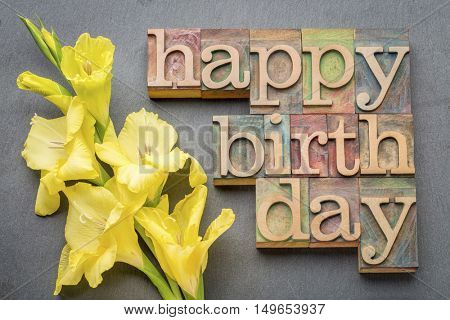 happy birthday greeting card - word abstract in letterpress wood type with a yellow gladiola flower against gray slate stone background
