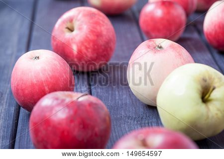 red ripe apples on wooden table close up