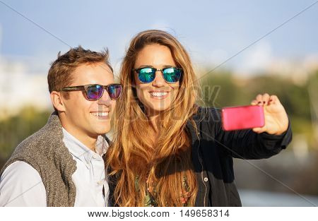 Young hipster couple taking selfie during honeymoon at the beginning of a love story. Traveler best friends having emotional fun together around Europe trip. Love concept with girlfriend dating guy.