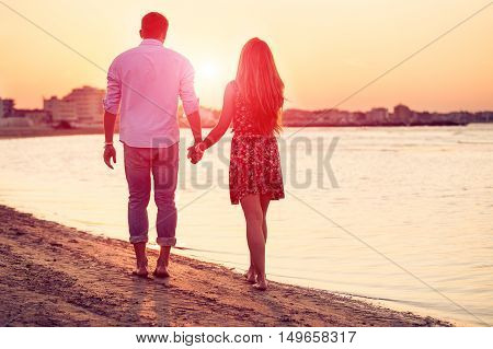 Rear view of happy couple holding hands standing against a beach side in summer. Two lovers in vacation in an idyllic nature scene sharing positive feelings and emotions. Magic moments of loving hearts.