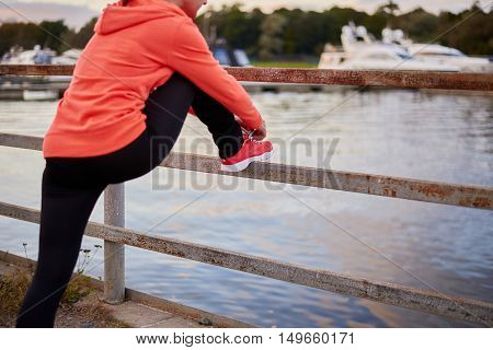 Woman tying shoe before running in sunny nature - sport and people healthy concept