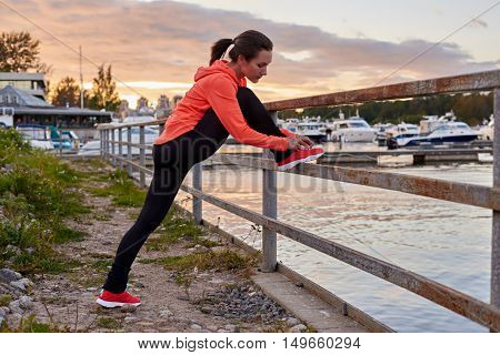 Fitness brunette have sport body. Beautiful girl tying her running shoes before jog. Sunset ocean day and yatch background. Concept of health life.