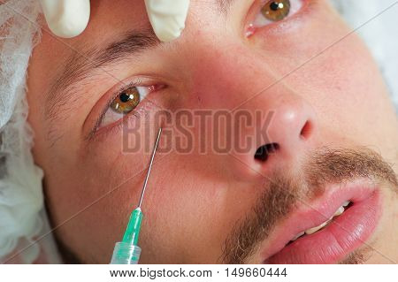 Closeup young mans face receiving facial cosmetic treatment injections, doctors hand with glove holding syringe.
