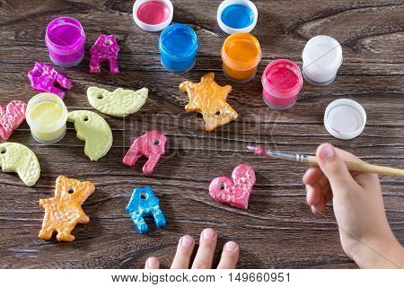 Child Painting Christmas Decorations From Salt Dough. Children's Art Project, A Craft For Children.