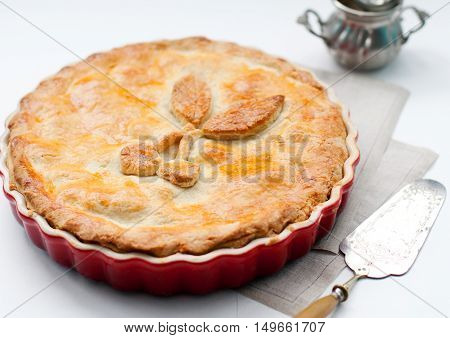 Cherry pie in a backing dish on a white background.