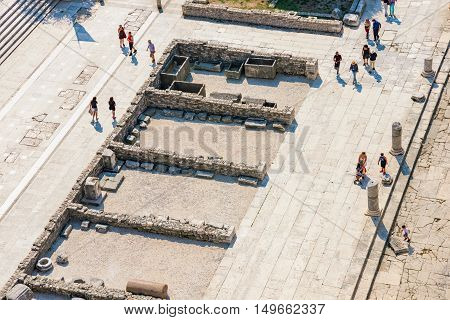 ZADAR CROATIA - SEPTEMBER 14: Birds eye view of tourists walking amongst the famous downtown ruins in the town center of Zadar on a hot sunny day on September 14th 2016 in Zadar