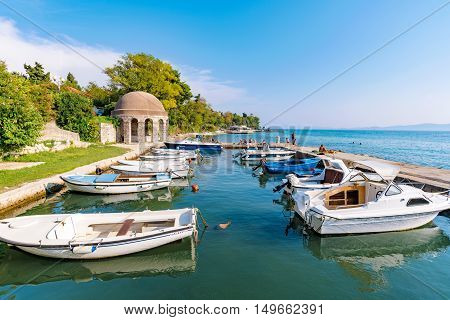 ZADAR CROATIA - SEPTEMBER 14: Harbor with boats and pier in the background where people have come to rlelax and swim on a hot sunny day on September 14th 2016 in Zadar