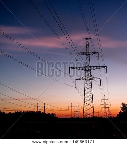 Electrical pylon and high voltage power lines at night