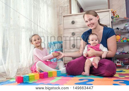 Little girl is enjoying her time at home playing games with her mother
