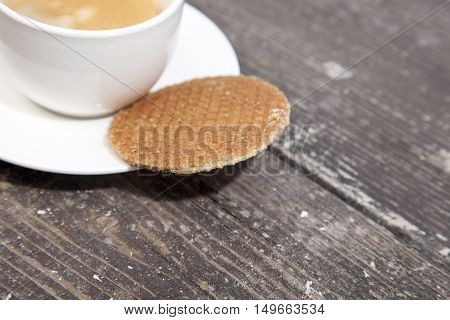 Dutch cookie stroopwafels with cup of coffee on brown wooden background