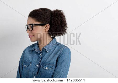Profile portrait of a young woman in glasses