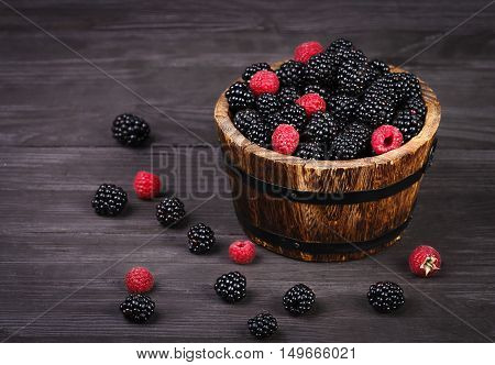 Berry raspberry and blackberry in basket at wooden board rustic style