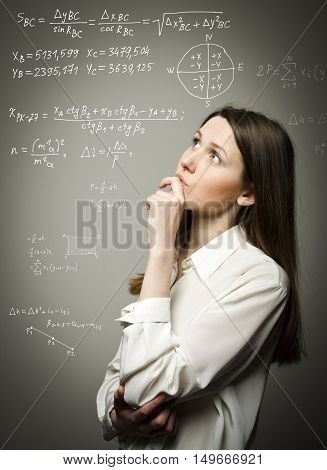 Thoughtful girl in white is solving equation. Thinking.