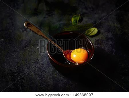 raw egg in a bowl, spoon, basil on a black background