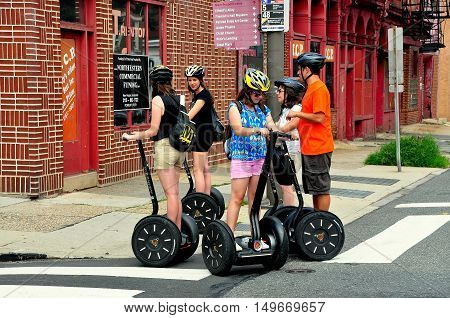Philadelphia Pennsylvania - June 25 2013: A group of tourists practise their skills on a two wheeled Segue before setting off to see the city's historic sights