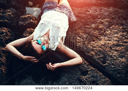 Pretty Brunette Girl Relaxing In The Stones