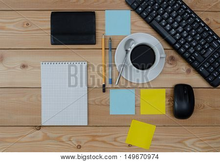 keyboard colored stickers cup of coffee wallet and office supplies laying on the board.