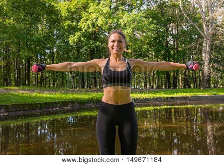 Sport woman doing exercises with dumbbells outdoors.