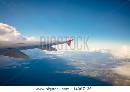 Aircraft wing flying over clouds, Sky and cloud above from airplane window