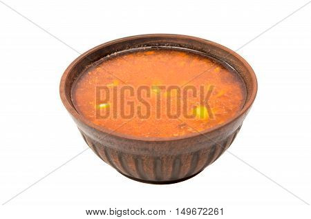 soup in a clay plate on a white background