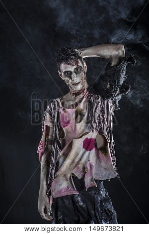 Male zombie standing on black background, looking at camera. Halloween theme