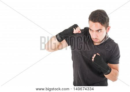 handsome latin fighter wearing black clothes training blocking isolated on white