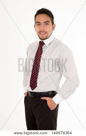 handsome latin man wearing a red tie with hands in pockets isolated over white