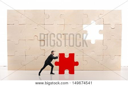Businessman complete a puzzle inserting a missing red piece