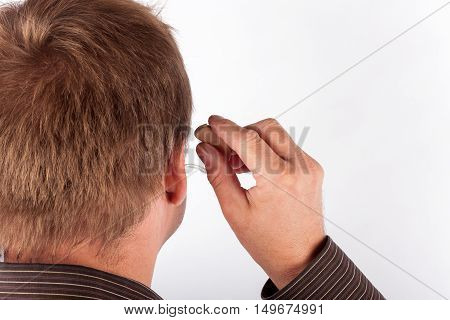 Middle aged man putting on or removing his hearing aid.